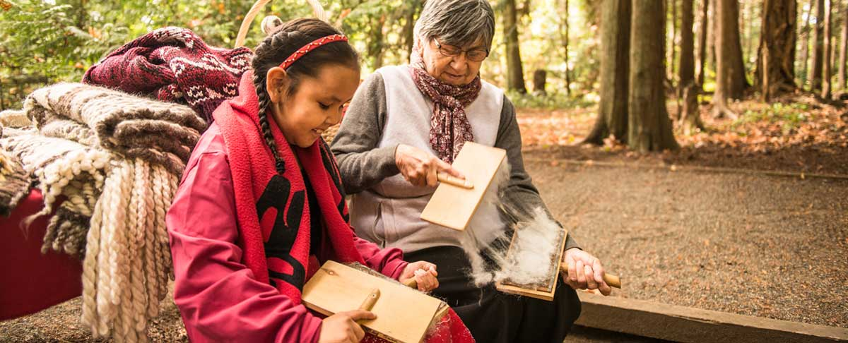 A First Nations girl and her grandmother demonstrate traditional knitting processes at McDonald Campground. Gulf Islands National Park Reserve Photo : Parks Canada/Scott Munn